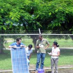 Participants performing measurements and experiments with solar water pumps.