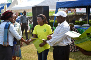 Sylvia Natukunda hands out participation certificates at the Agri-Profocus Marketplace event in Uganda.