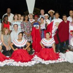 Members of Kellogg Foundation pose with students in traditional dress after cultural presentation.