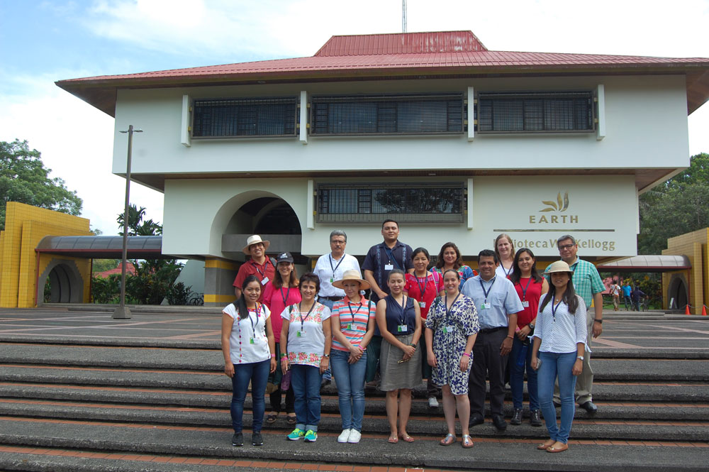 The WKKF visitors stand alongside members of the EARTH University Office of Development, in front of the W.K. Kellogg Library on EARTH's campus in Guácimo, Costa Rica.