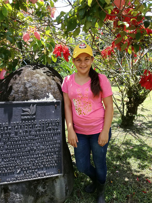 Ángela stands beside the plaque at the Integrated Organic Farm.