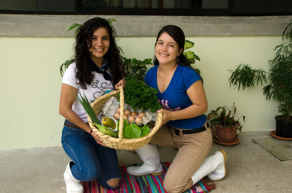 Carolina and Johana display a basket full of local products, organized by Cultivarme.