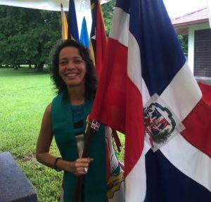 Picture of a woman smilling holding a flag. Trees on the back