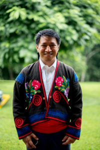 Picture of a man smiling, wearing traditional Guatemalan cloth. Behind him trees
